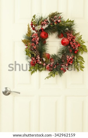 Close-up of Christmas wreath decoration with red apples and berries on a white wooden door with handle  - stock photo