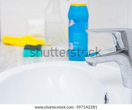 Close up of chrome sink spigot and cleaning chemicals, bottle, sponge and yellow rag with copy space - stock photo