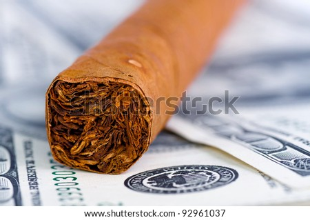 Close-up of cigar on the hundred Dollars bills - stock photo