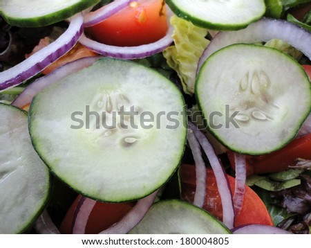 Close-up of Classic Garden Salad featuring Cucumbers, onions, tomatos, and lettuce.