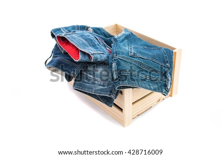 Close up of classic japan denim jean in wooden box on white background isolated.