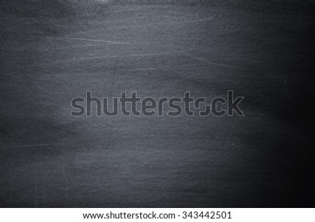 Close up of clean school blackboard. Chalk rubbed out on black horizontal chalkboard. Blackboard or chalkboard texture. Grunge background. - stock photo