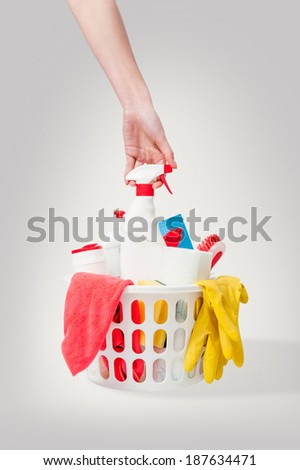 Close up of cleaning products and supplies in a basket and hand taking the window cleaner spray bottle. Cleaners, microfiber cloths, gloves in a basket isolated on white background. Cleaning kit. - stock photo