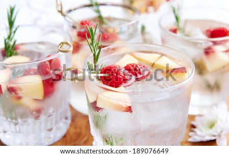 Close up of clear cocktails/soda water being served on a wooden tray decorated with flowers, raspberries, sliced nectarine and rosemary garnish - stock photo