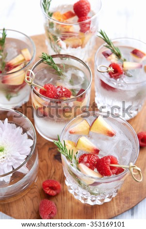 Close up of clear cocktails/soda water being served on a wooden tray decorated with flowers, raspberries, sliced apples and garnish - stock photo