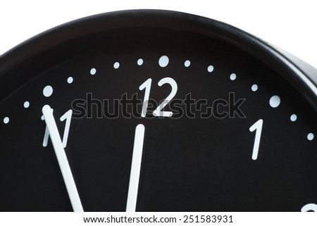 Close up of clock face showing the hands at five minutes to midnight - stock photo