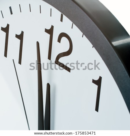 Close up of clock face showing the hands at two minutes to midday - stock photo