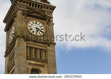 Close up of clock tower against a blue sky