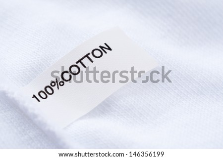 Close up of cloth tag 100% cotton on white fabric - stock photo