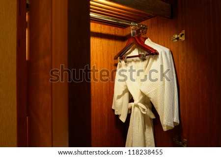 Close up of clothes hanger and twins bathrobe in wooden wardrobe in hotel - stock photo