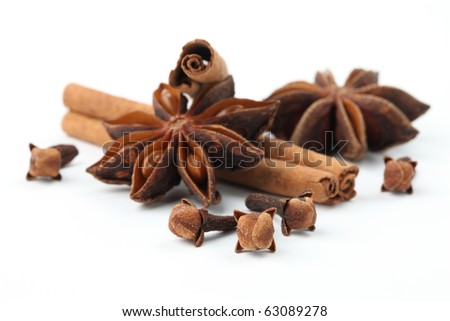 Close-up of cloves, anise and cinnamon on white background. Shallow dof - stock photo