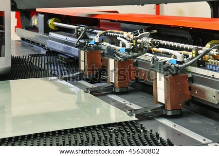 close up of cnc punching machine with metal plate - stock photo