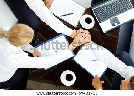 Close-up  of co-workers making pile of hands at meeting - stock photo