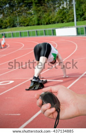 Close up of coach is holding a stopwatch against concentrated man waiting in starting block