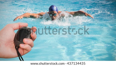 Close up of coach is holding a stopwatch against fit swimmer doing the butterfly stroke in the swimming pool
