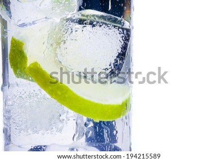 close-up of cocktail glass with ice and lime slice isolated on white background and space for text - stock photo