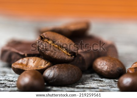 close up of coffee beans and  chocolate on wooden background - stock photo