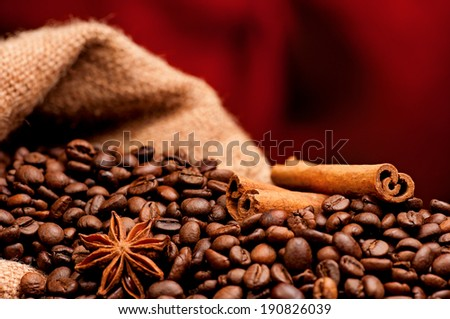 Close-up of coffee beans in burlap sack on dark red background - stock photo