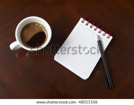 close up of coffee cup and notebook with pencil on table - stock photo