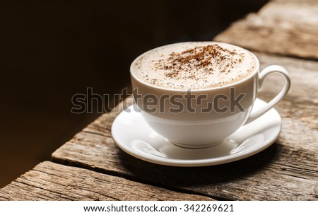 Close-up of coffee cup  on wooden background. - stock photo