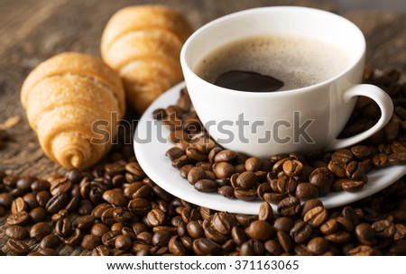 Close-up of coffee cup with roasted coffee beans on wooden background.
