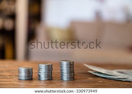 Close-up Of Coins Stack On Wooden Table - stock photo