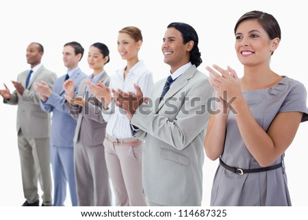 Close-up of colleagues smiling and applauding with focus on the first two people against white background - stock photo