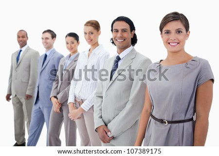 Close-up of colleagues smiling and looking straight with focus on the first two people against white background