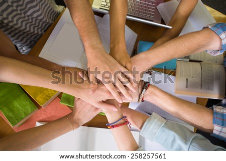 Close up of college students placing hands together over library table - stock photo