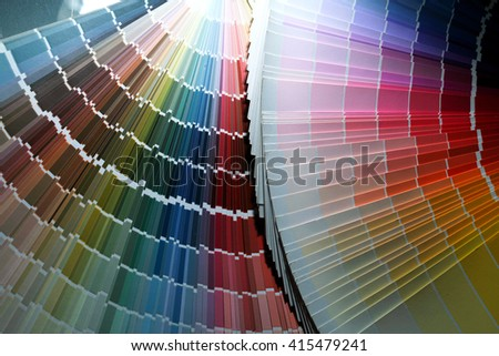 close-up of color guide spread out like a fan on a dark background studio - stock photo