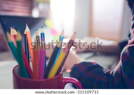 Close-up of colored pencils in mug with businessman working in background - stock photo
