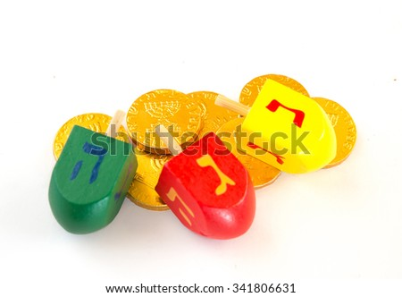 Close up of colored wood dreidels and Chocolate coins for Hanuka celebration.  Variable focus. - stock photo