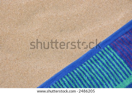 Close up of colorful beach towel on rippled sand - stock photo