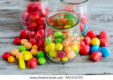 Close-up of colorful bright candies in glass jars and scattered on table - stock photo