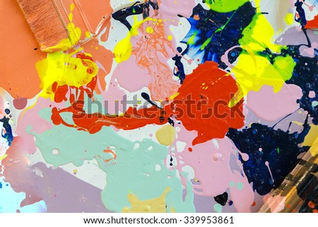 Close up of colorful dirty used color plate and brush. - stock photo
