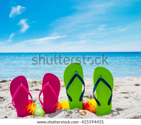 close up of colorful flip flops on the sand - stock photo