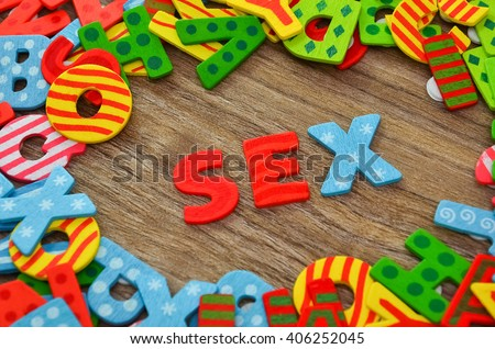 Close up of colorful font with the word Sex against wooden background. Selective focus.