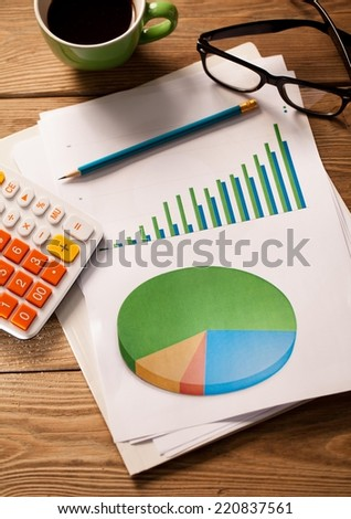 Close up of colorful graphs and calculator. - stock photo