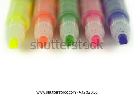 Close up of colorful highlighters lined up isolated on white - stock photo