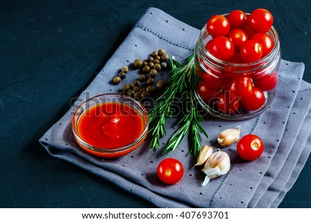 Close up of colorful ingredients for cooking cherry tomato sauce on dark rustic background, selective focus. Vegetarian eating. Fresh harvest from the garden. - stock photo