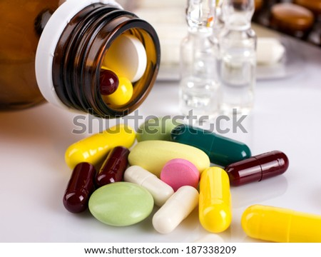 close-up of colorful medical tablet and ampules from glass bottle on blurred drugs and white background