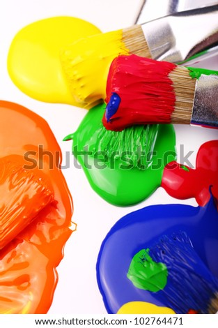 Close up of colorful paint and brushes - stock photo