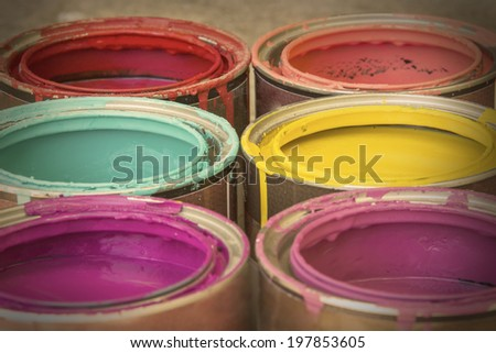 Close up of colorful paint in cans buckets tins with retro vintage filter - stock photo