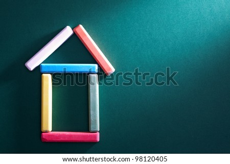 Close-up of colorful pieces of chalk put in form of house on blackboard - stock photo