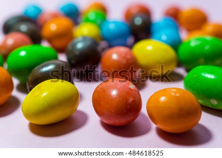 Close up of colorful round candy on pink background
