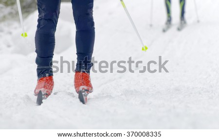 Close up of colorful skies, feet and legs of two cross country skiers - stock photo