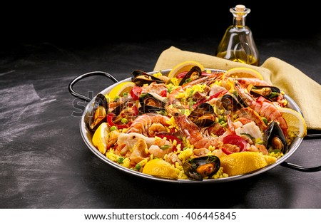 Close Up of Colorful Spanish Seafood Paella Rice Dish with Fresh Shellfish Served with Lemon Wedges in Pan on Smudged Chalkboard Background with Oil and Napkin - stock photo