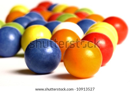 close-up of colorful spherical chewing gum over white background