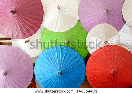 Close up of colorful umbrellas with wooden handle at Bo Sang Umbrella Village, Chaing Mai, Thailand - stock photo