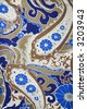 Close-up of colorful vintage fabric with blue and brown paisley printed on polyester. - stock photo